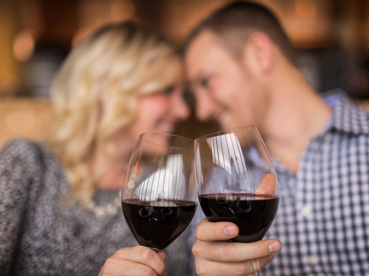 blurred couple clinking wine glasses